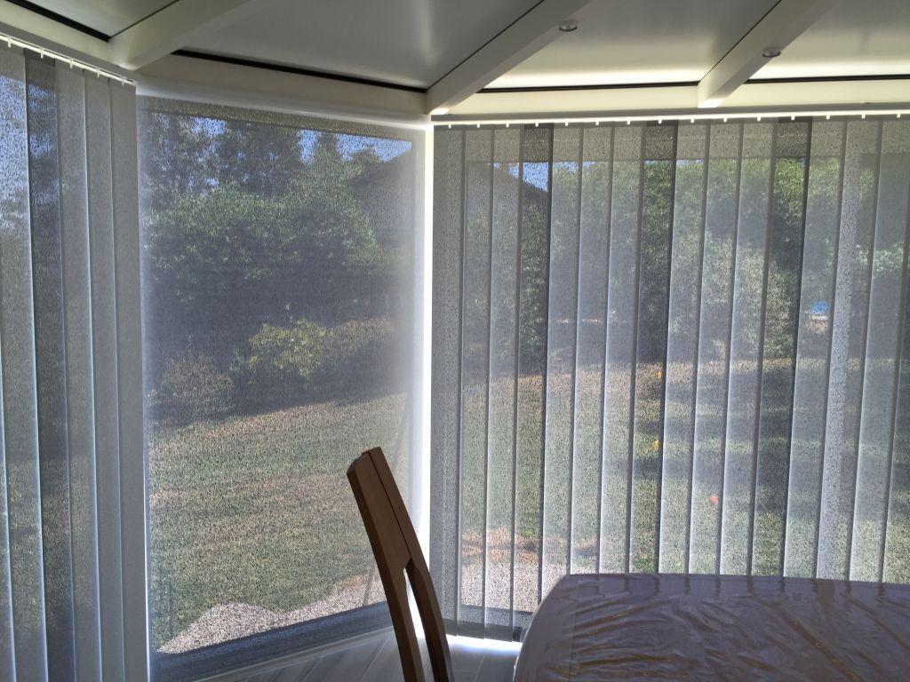 Stores enrouleurs et à bandes verticales avec toile microperforée métallisée pour protéger une véranda. aux de reflexion solaire de 83%.    …