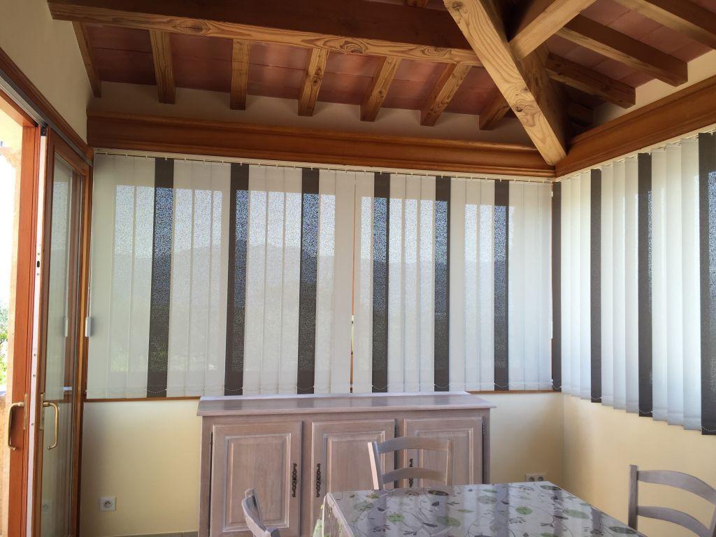 Maison provençale équipée de stores de protection solaire, bandes verticales avec panachage, toile microperforée métallisée, taux de réflexion solaire de 83%.    …